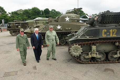 Charles Lavine and Museum workers in front of tanks