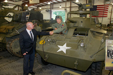 Fred Daum greets driver of tank in Museum of American Armor warehouse