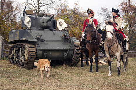 Military Timeline Event with Riders on Horseback with tank and a dog leading the way.